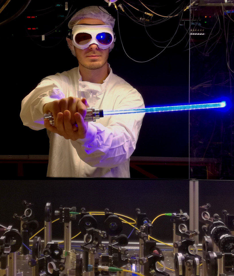 <p><em>Doctoral candidate Nicolas Tolazzi holding a toy light saber in front of the experiment. <br /></em></p>